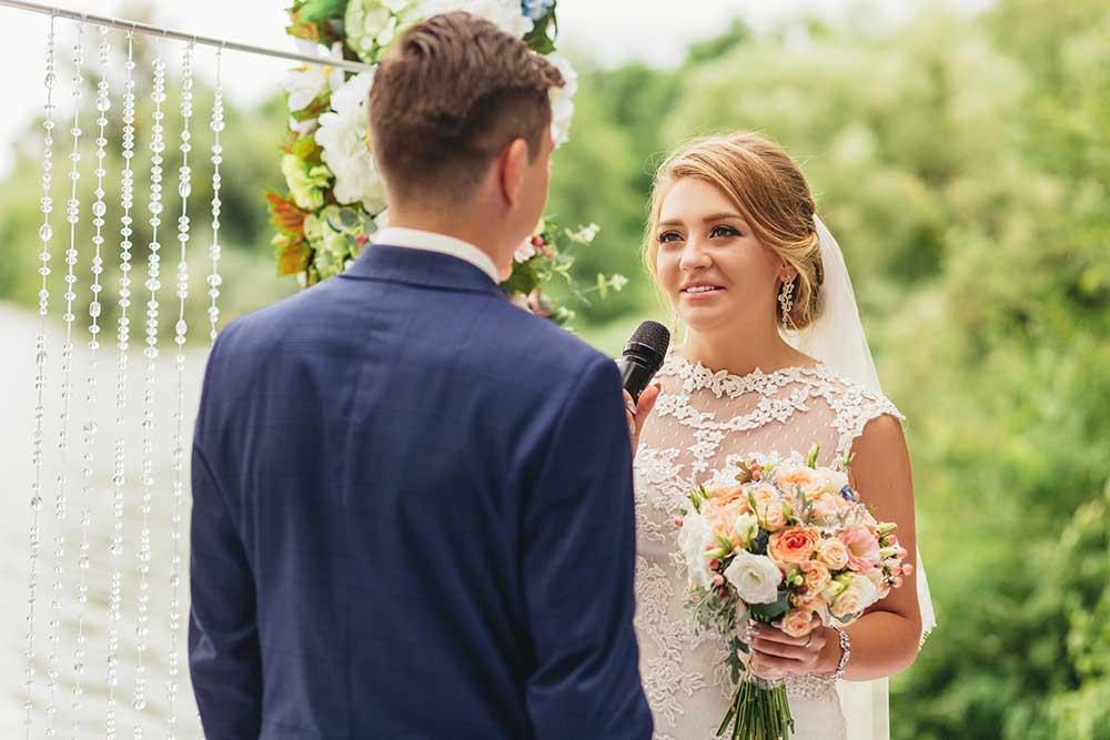 結婚式で結婚の誓いを述べる新婦とそれに向かい合う新郎