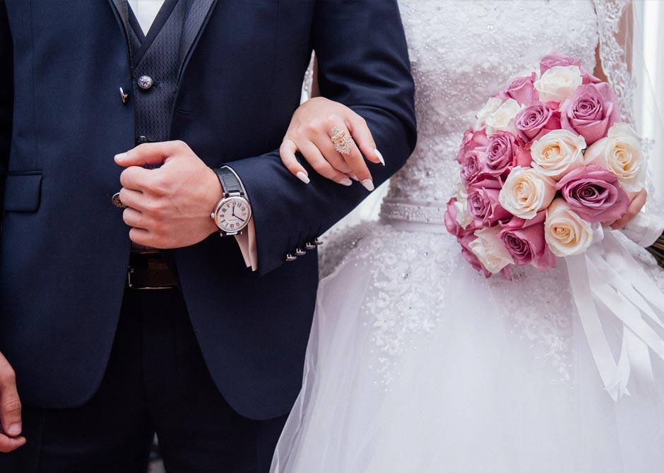 タキシードとウエディングドレスを着た新郎新婦が腕をくんでいる写真
