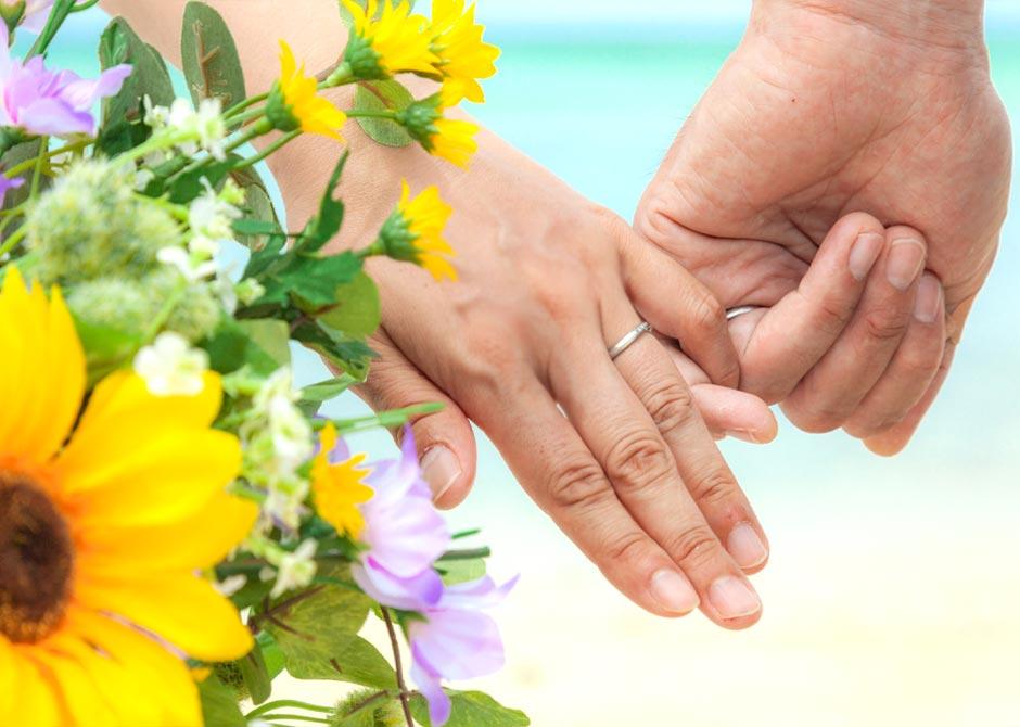 黄色や白の花とゆびきりをする夫婦