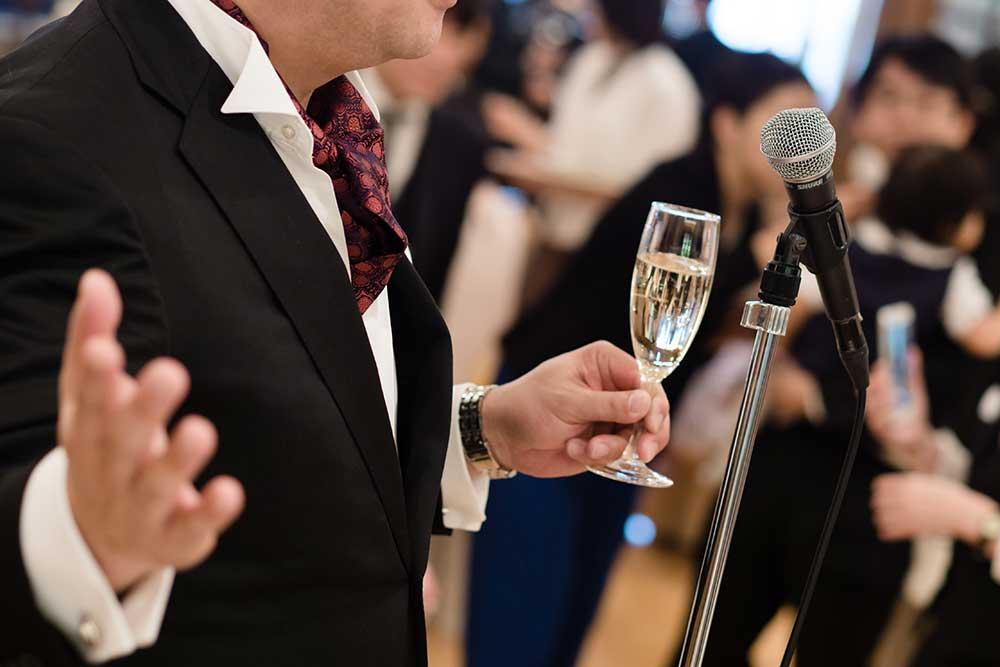 シャンパングラスを手にマイクの前で乾杯の挨拶をしている男性