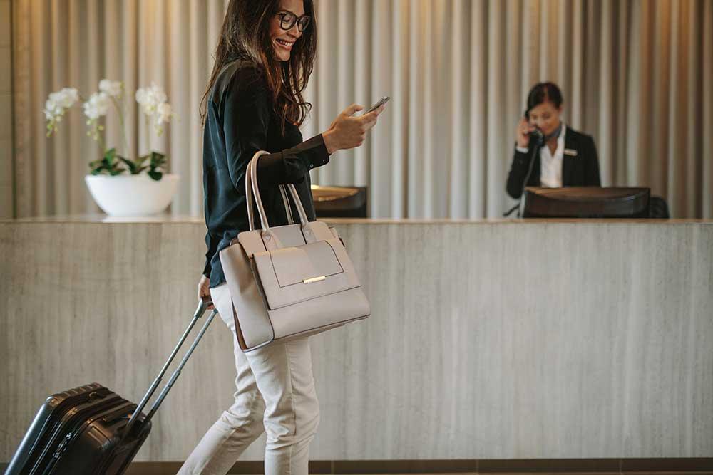 ホテルのフロントでチェックインしようとしている女性