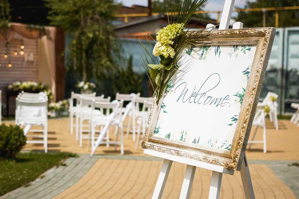 結婚式会場に入り口に置かれたゴールドフレームに植物を飾りつけたウェルカムボード