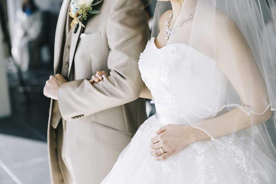 家族婚にて新郎と新婦が腕を組んで立っている