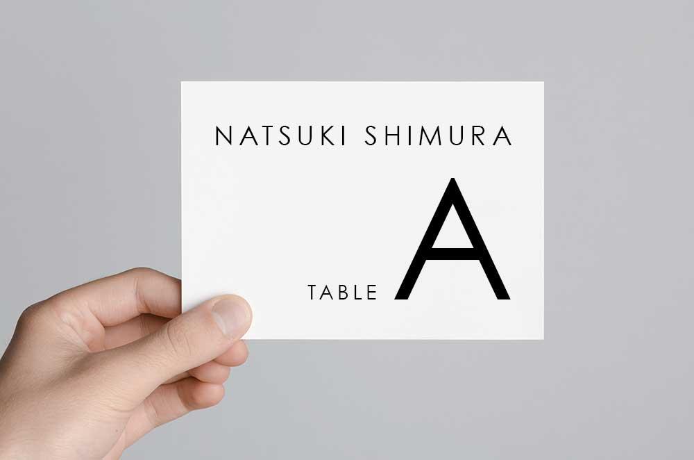 名前とテーブルナンバーが書かれたシンプルなエスコートカードを持つ手