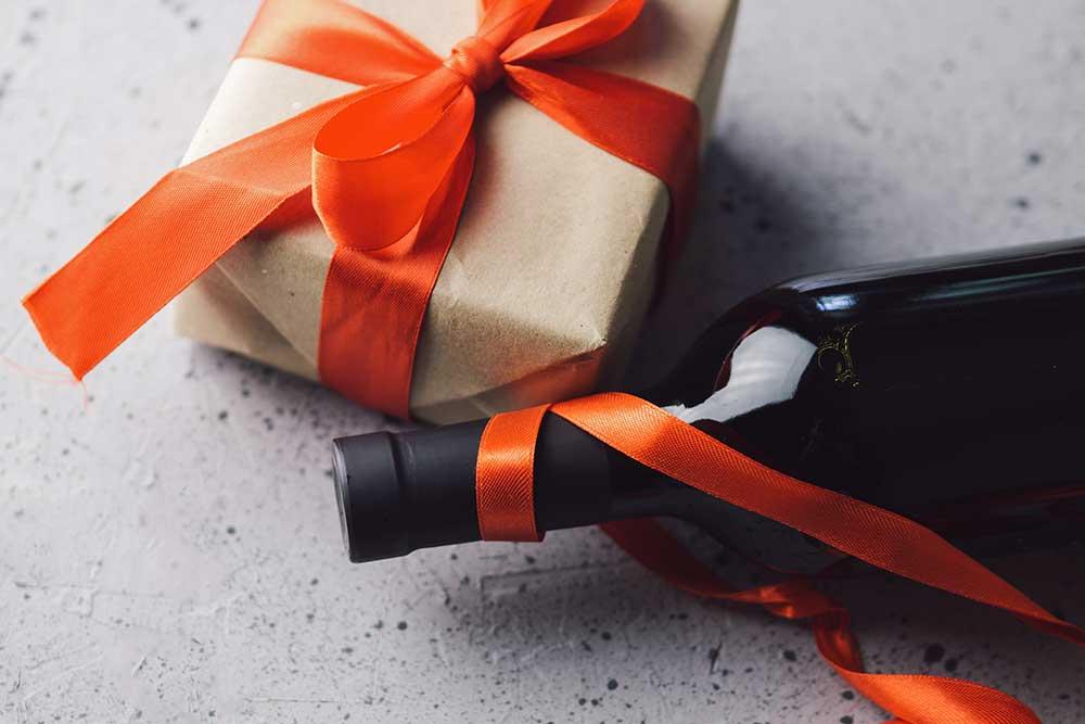 オレンジのリボンでラッピングしたギフトボックスとワイン