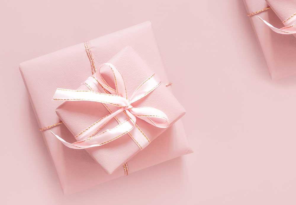 ピンクのラッピングペーパーとリボンで包装されたギフトボックス