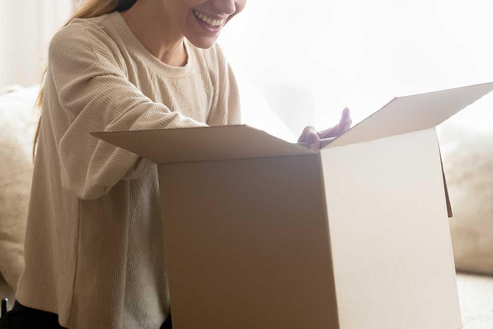 笑顔で段ボール箱の中身を確認している女性