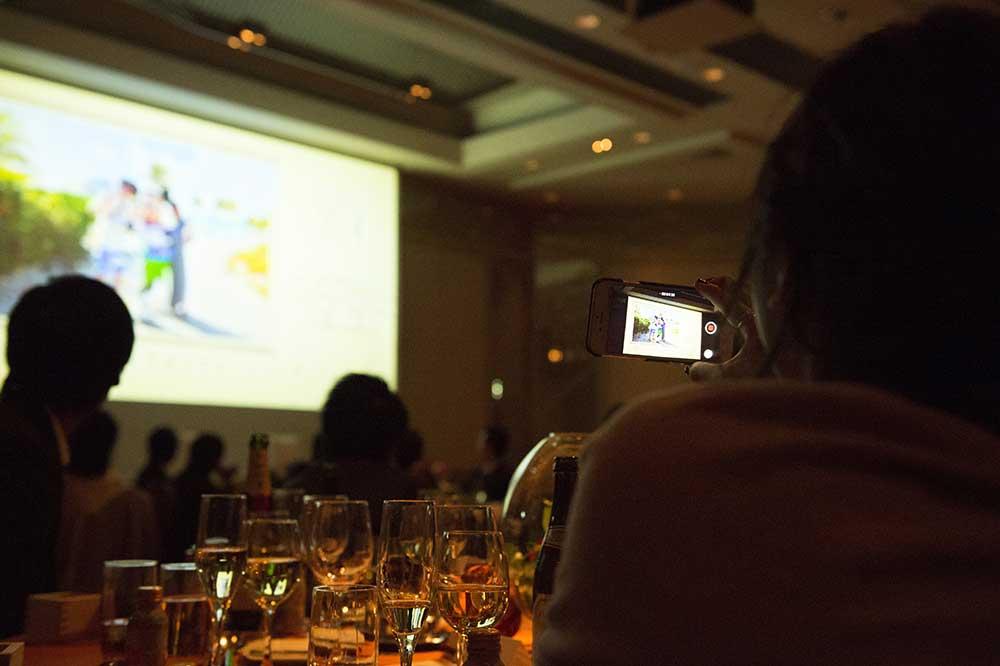 披露宴会場のプロジェクターで映像を見るゲストの様子