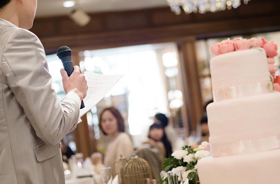 結婚式の披露宴会場で手紙を読む新郎