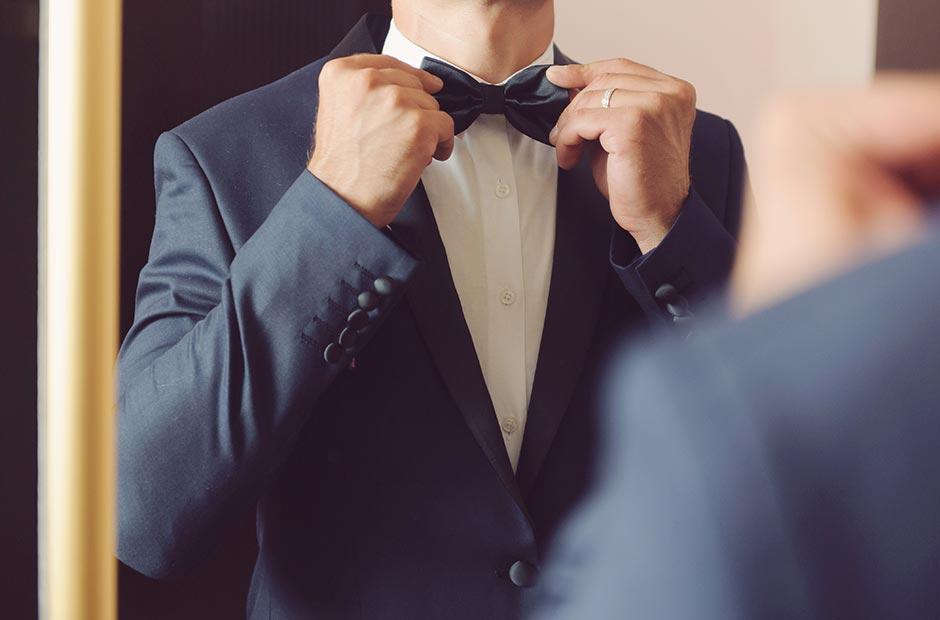 結婚式で蝶ネクタイを結びなおす新郎