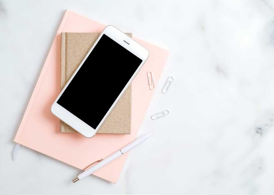 大理石の上のピンクのノートとスマートフォン
