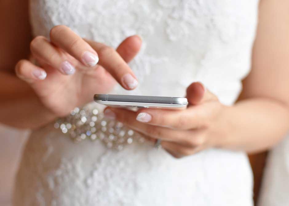 スマートフォンを操作するウェディングドレス姿の花嫁