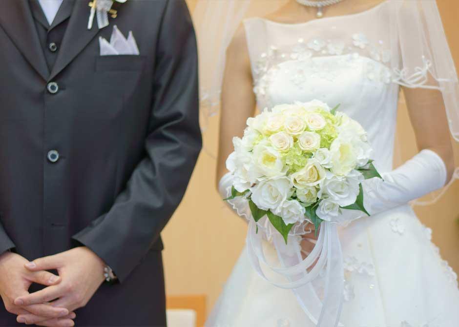 結婚式でブーケを持つ花嫁と横に立つ新郎