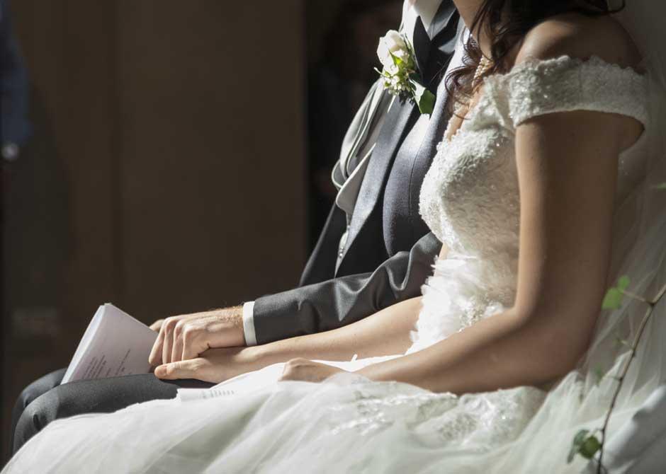 結婚式で挨拶スピーチをの原稿を持つ新郎と手を握る新婦