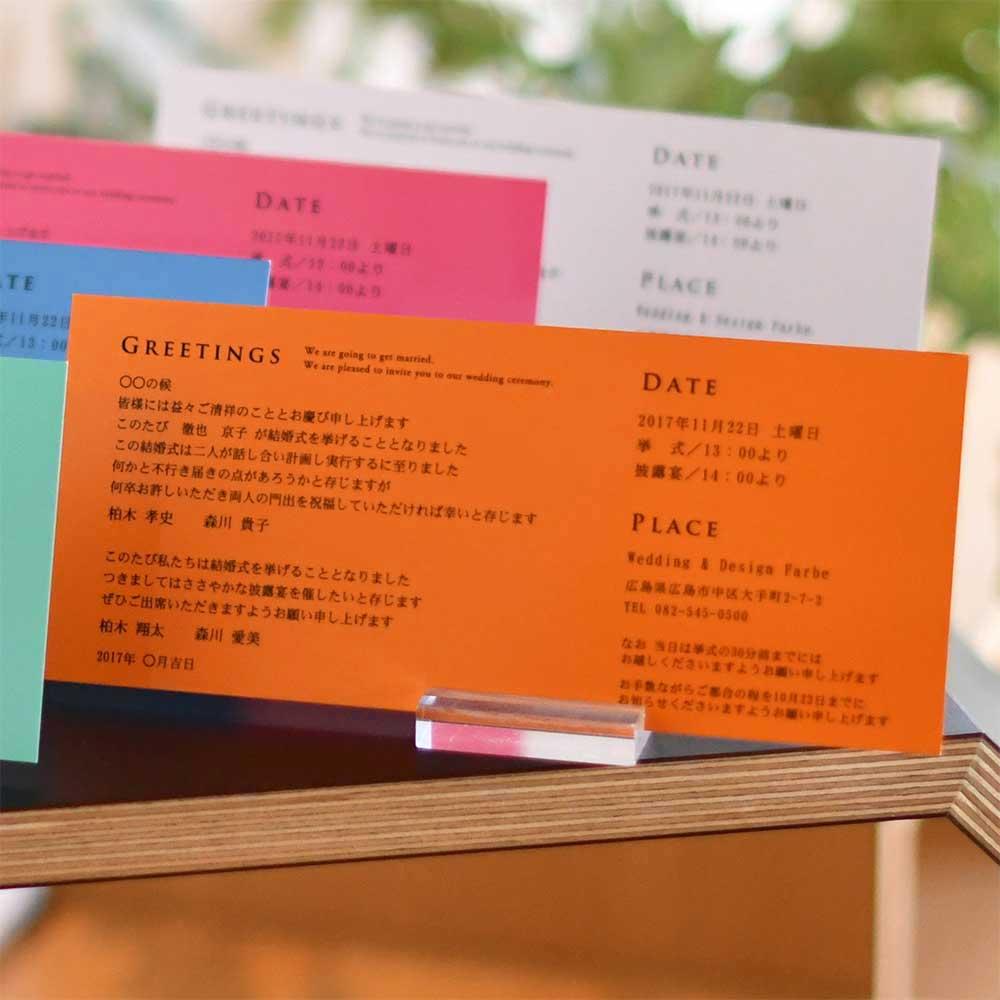 横長フォルムの台紙を開くと、トレーシングペーパーが本状に重ねられて。おふたりのイニシャル、挙式日入りのオリジナルな招待状