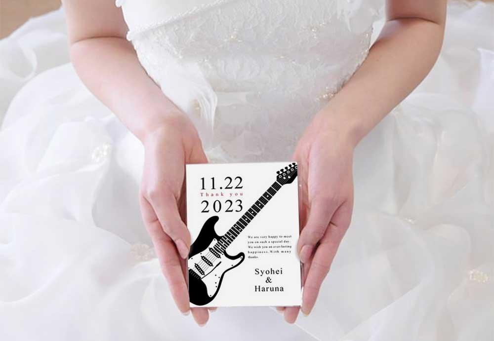 楽器デザインのプチギフトを手に持つ花嫁