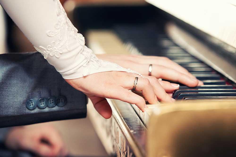 ピアノを連弾する新郎新婦の手元