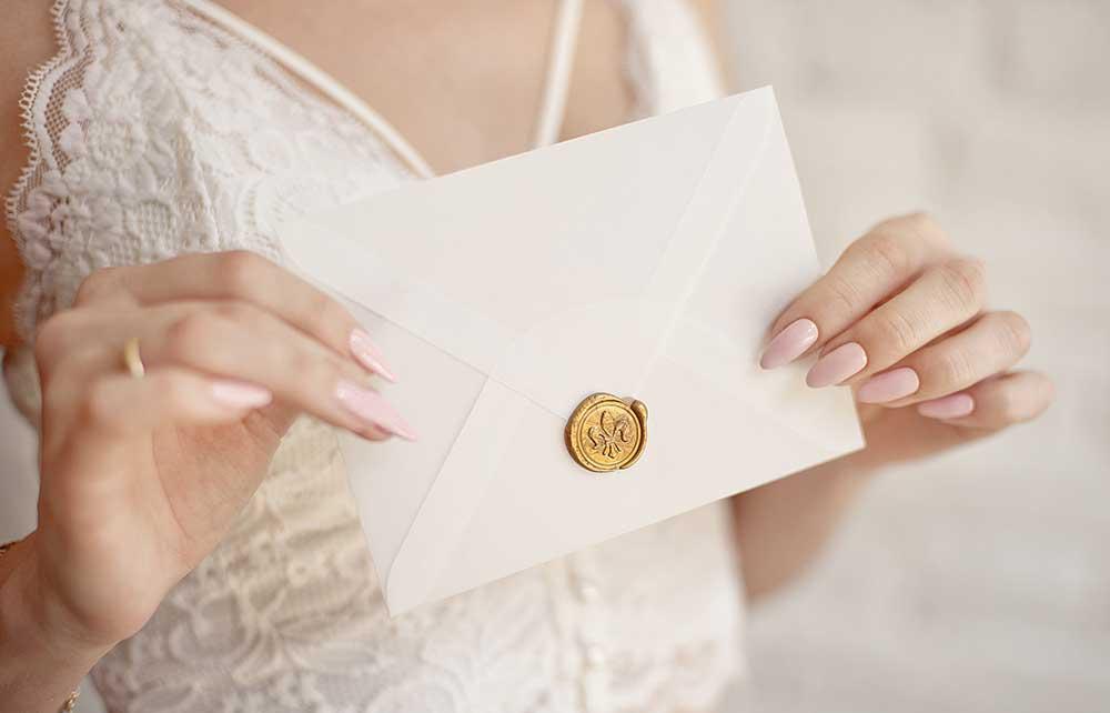 結婚式の招待状を手に持つ女性