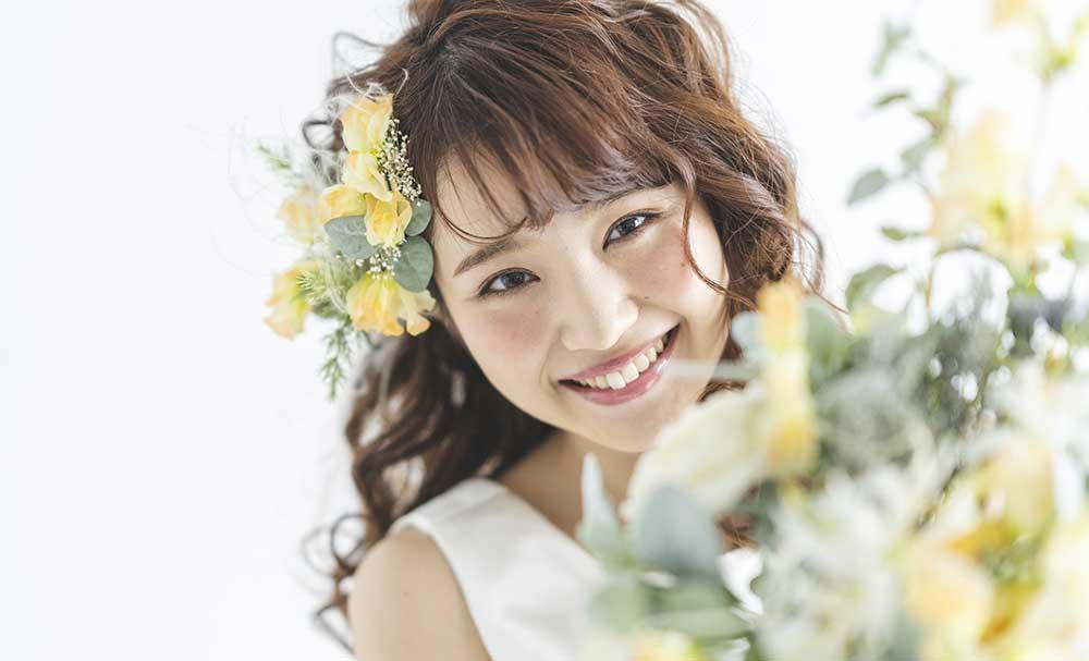 黄色のブーケと髪飾りを付けてほほ笑む花嫁