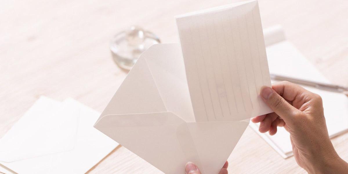 封筒にメッセージを書いた便せんを入れている
