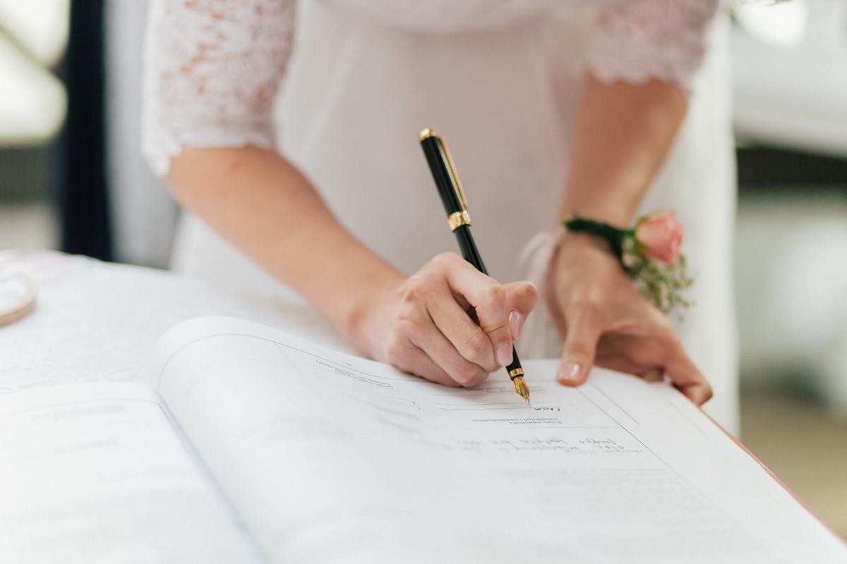結婚証明書にサインをしているウェディングドレスを着た花嫁