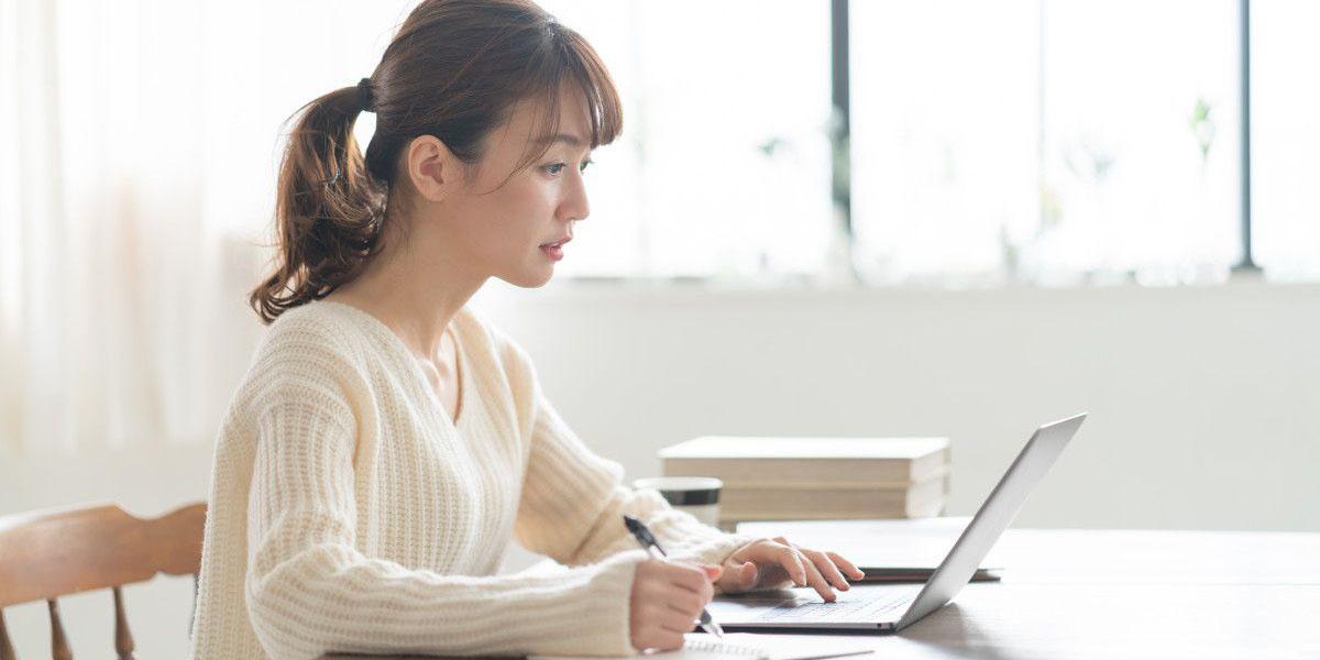 パソコンを見ながらメモを取る女性