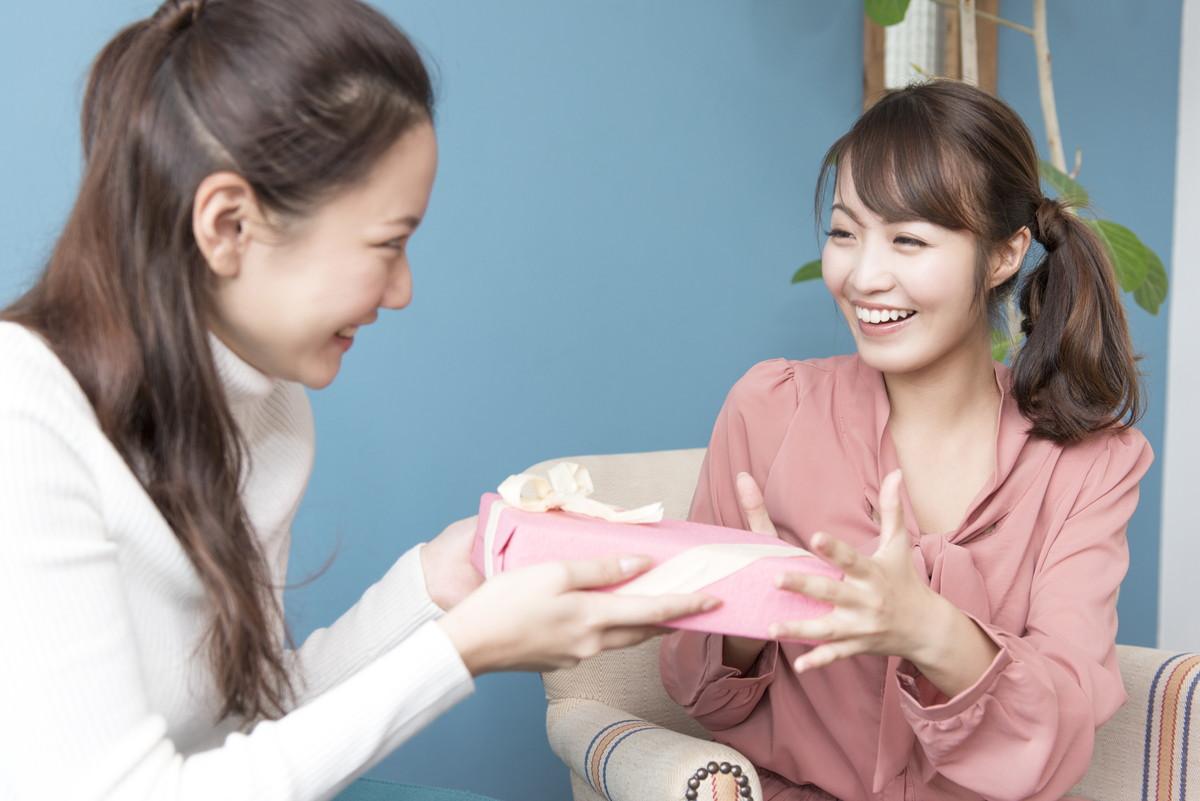 友人にプレゼントを渡している女性