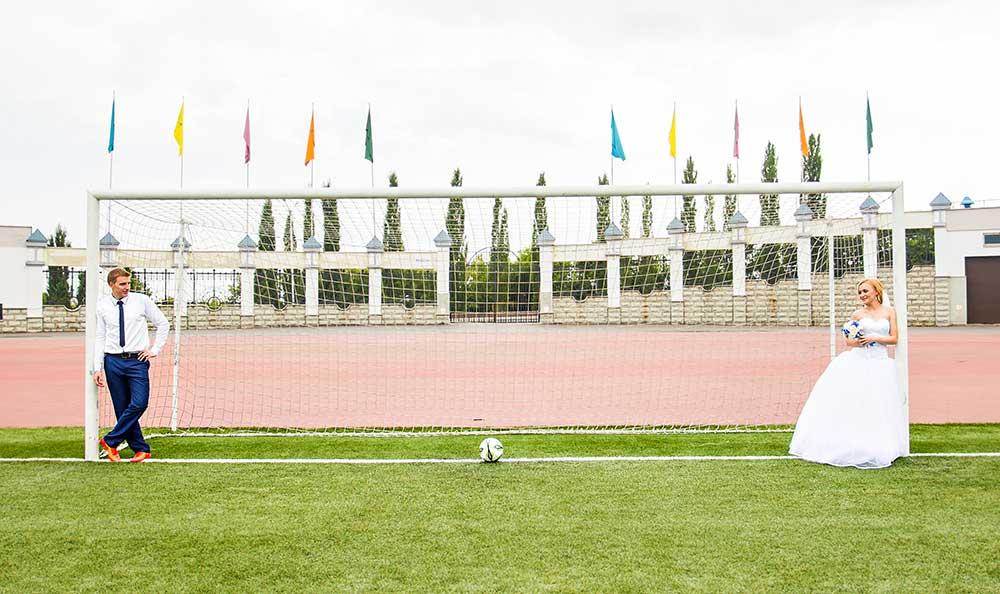 サッカーゴールの前で写真を撮る新郎新婦