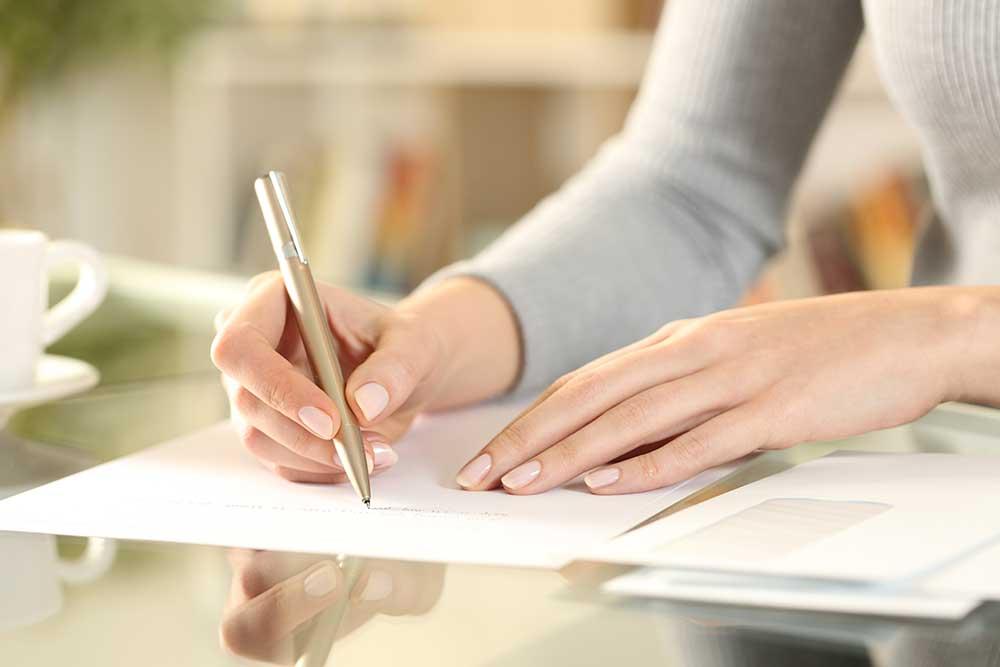 手紙を便箋に書く女性