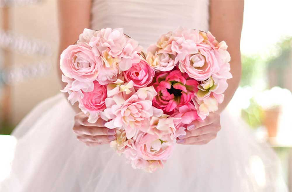 ピンクのフラワーアレンジが付いたお手紙ボードを両手で持つ花嫁