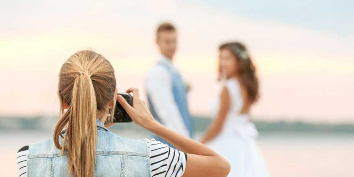 海岸で前撮り写真を撮ってもらっているカップル