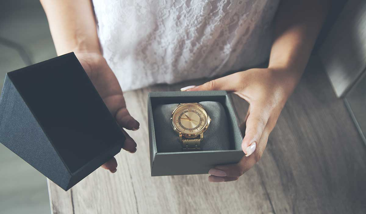 時計のプレゼントの箱を開けている女性