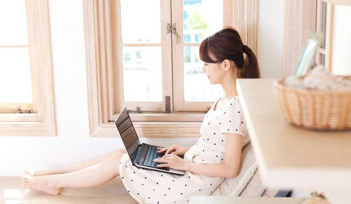 窓際のソファに座ってノートパソコンで作業する女性