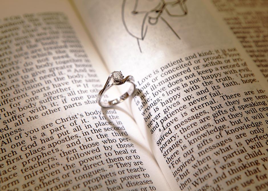 英語の本の間に置いた婚約指輪の影がハートのかたちになっている