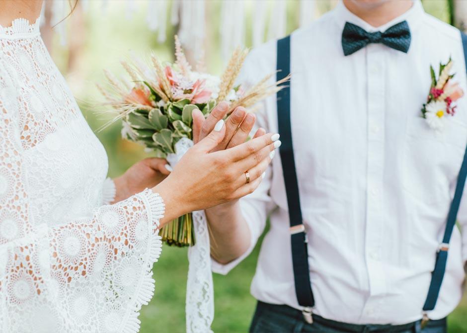 スワッグブーケを持つ花嫁と蝶ネクタイをした花婿