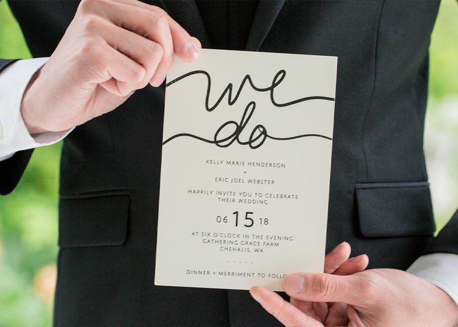 結婚式の日付が大きく書かれた招待状を持っている男性