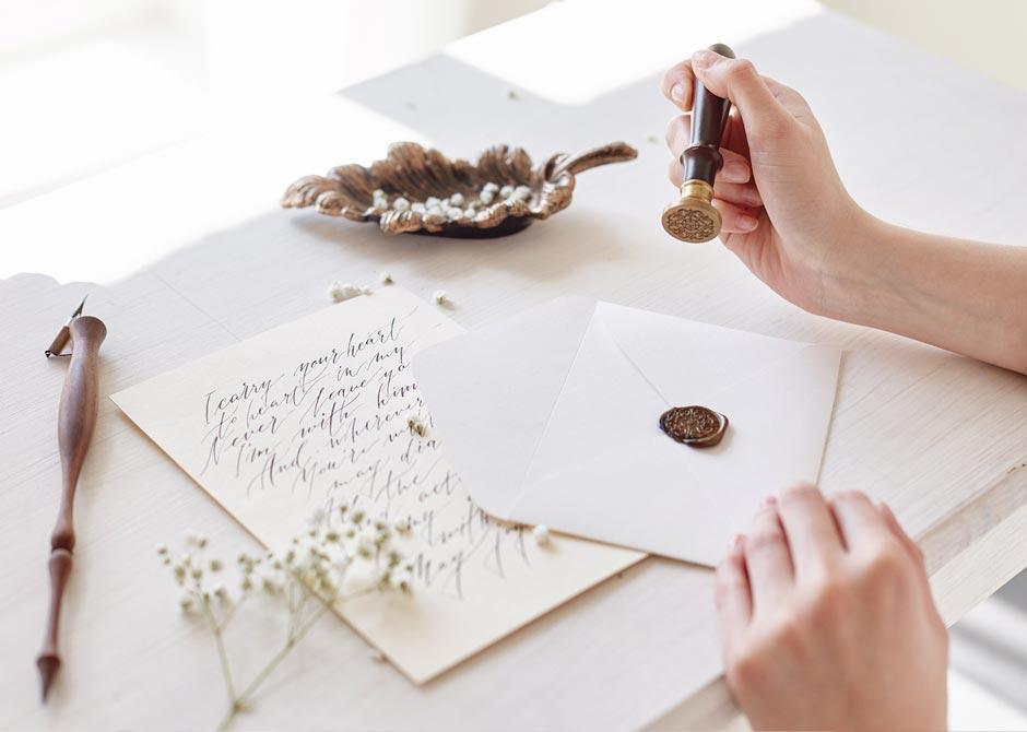 手紙を書いて封筒にシーリングスタンプを押している