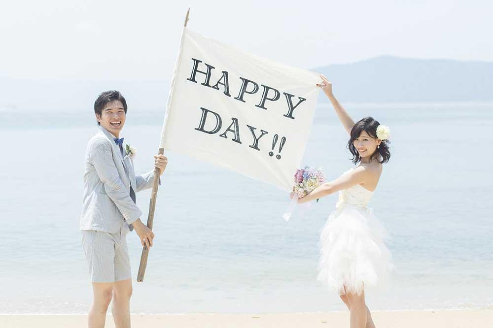 HAPPYDAYのフラッグを掲げて海辺で写真を撮る新郎新婦