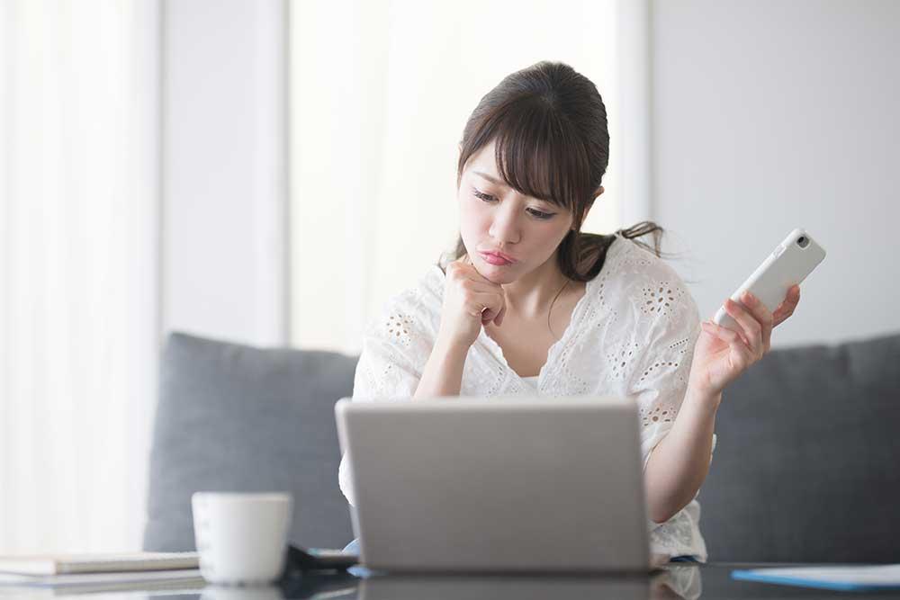 パソコンとスマホを持って悩んでいる女性