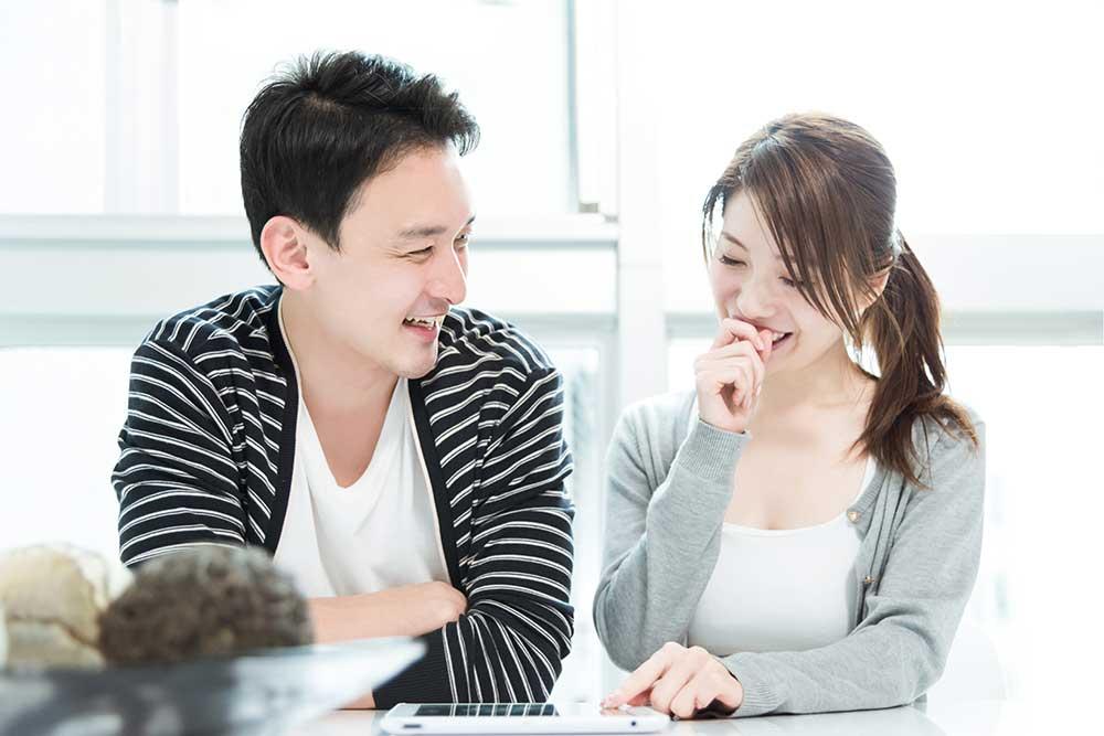 笑顔でタブレットを見ている男女カップル