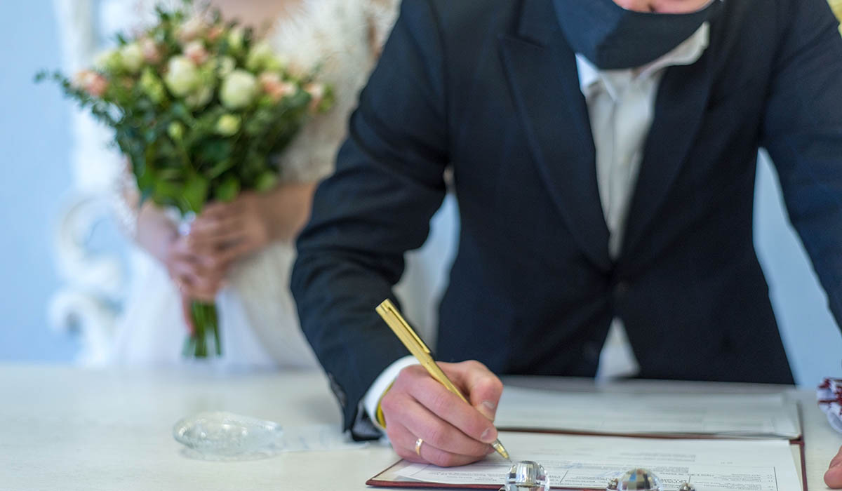 マスクをして結婚証明書にサインする新郎