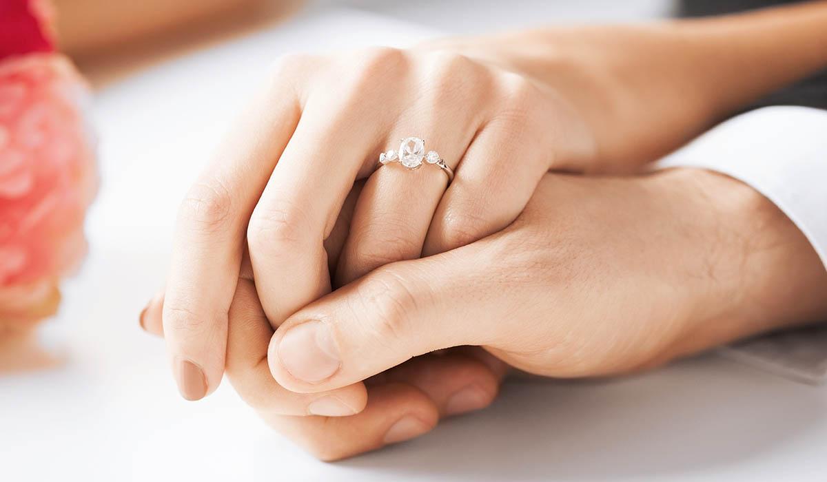 婚約指輪をつけた新婦の手を新郎が手を握っている