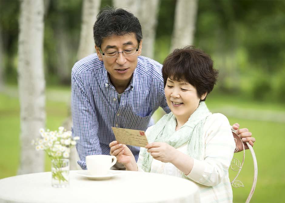 親戚からの結婚報告はがきを見ている夫婦