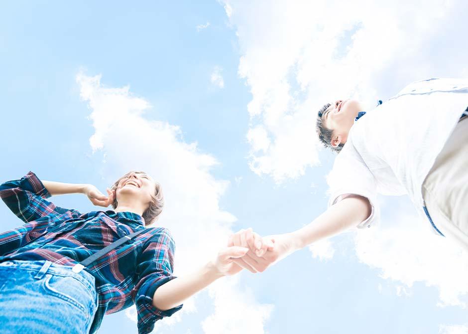 青空の下で手をつなぐ笑顔のカップル