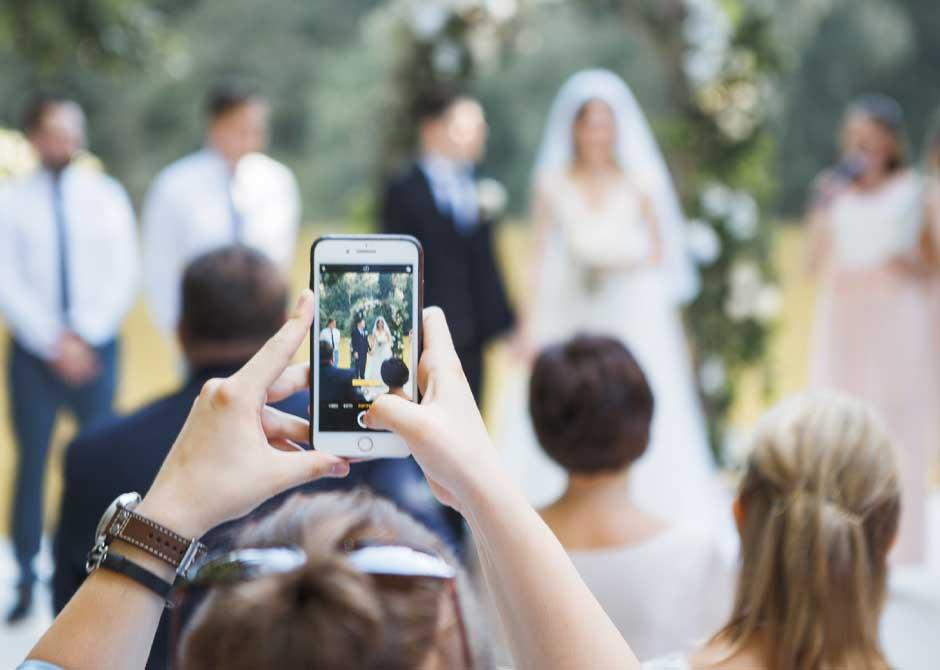 スマホで新郎新婦の写真を撮っている結婚式のゲスト