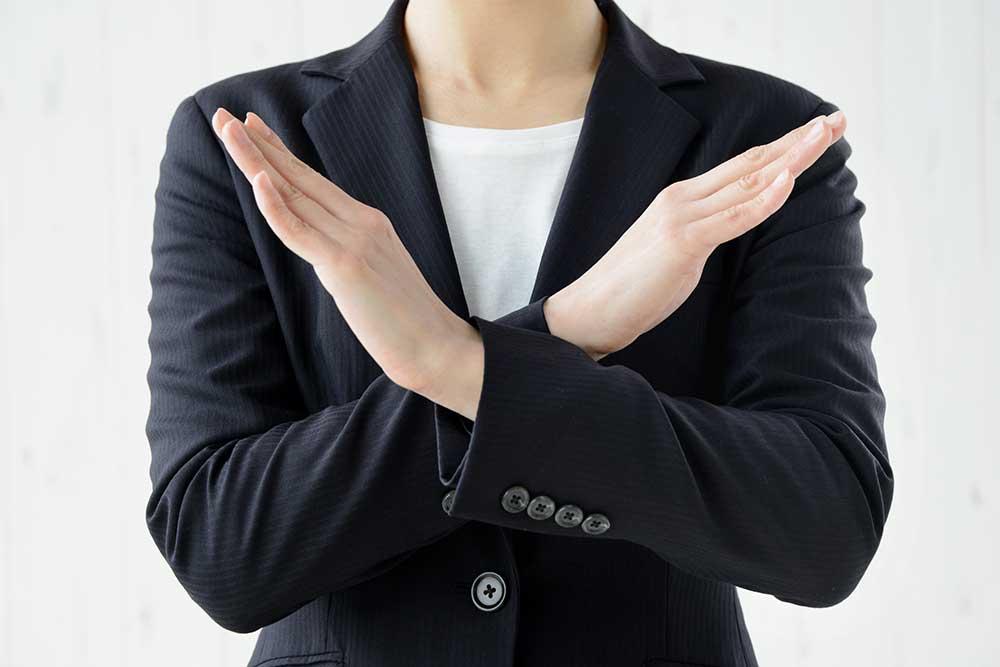 手の前でバツ印を作るスーツの女性