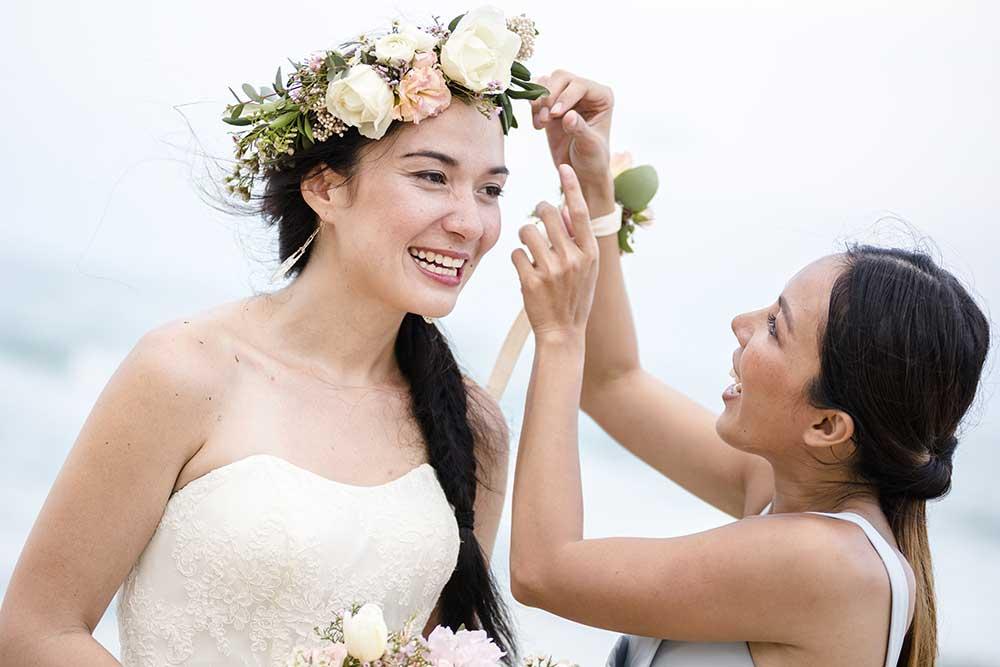 花嫁に花かんむりをつける姉妹