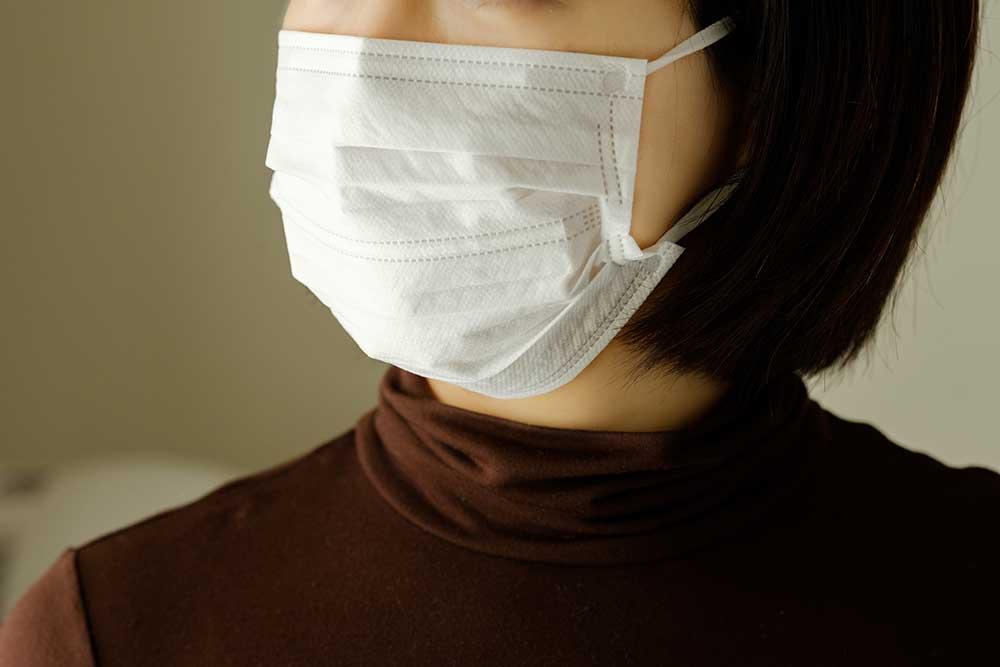 感染症対策のための不織布マスクをつけた女性