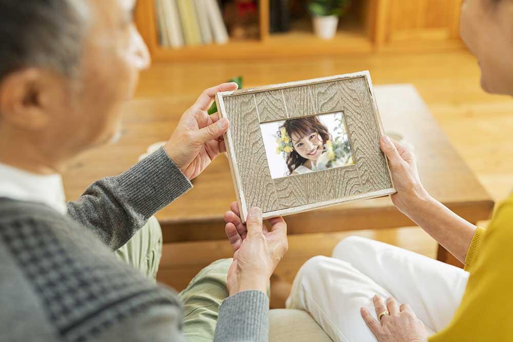 孫の花嫁姿の写真を見ている祖父母