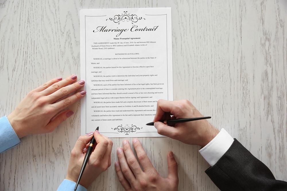 二人でサインする結婚証明書